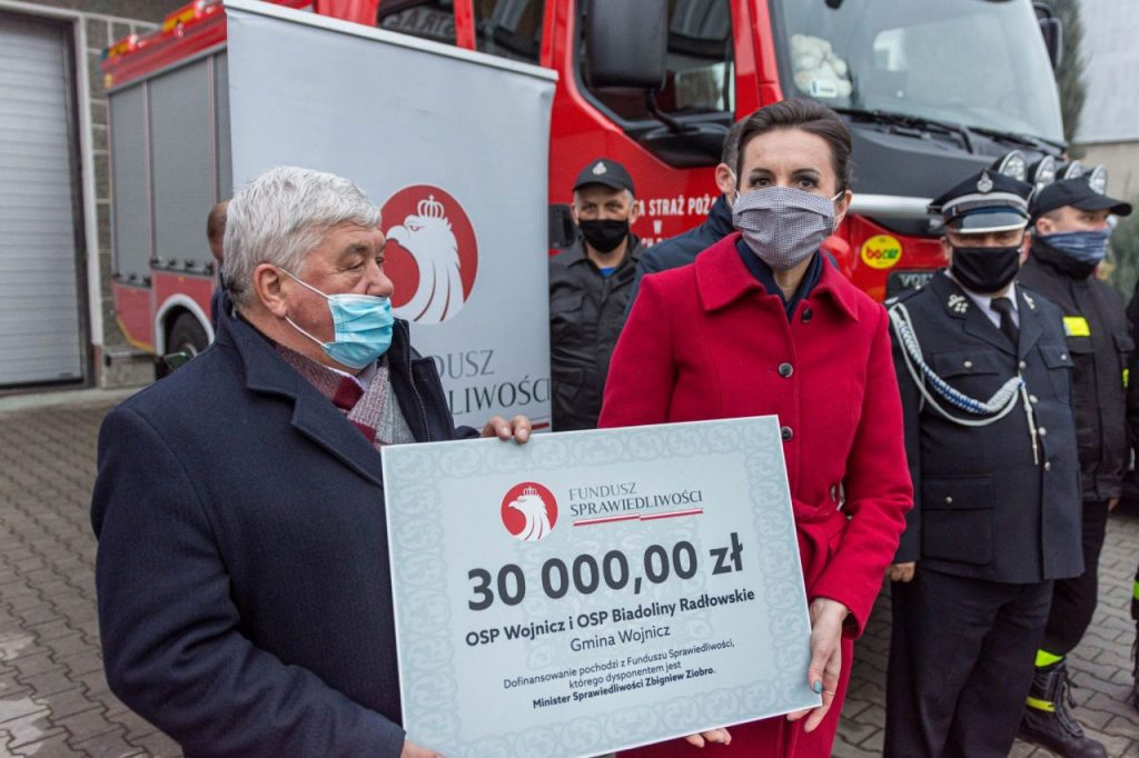Burmistrz Wojnicza w otoczeniu strażaków przekazujący promesę na zakup sprzętu