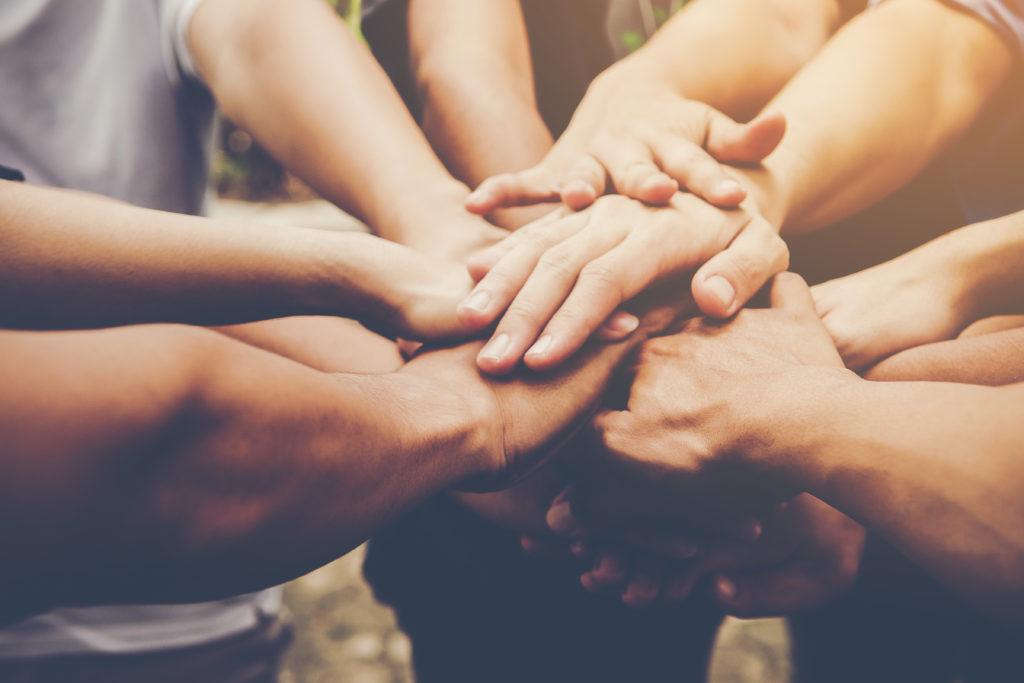 Zdjęcie złożonych kilku rąk symbolizujące współpracę.