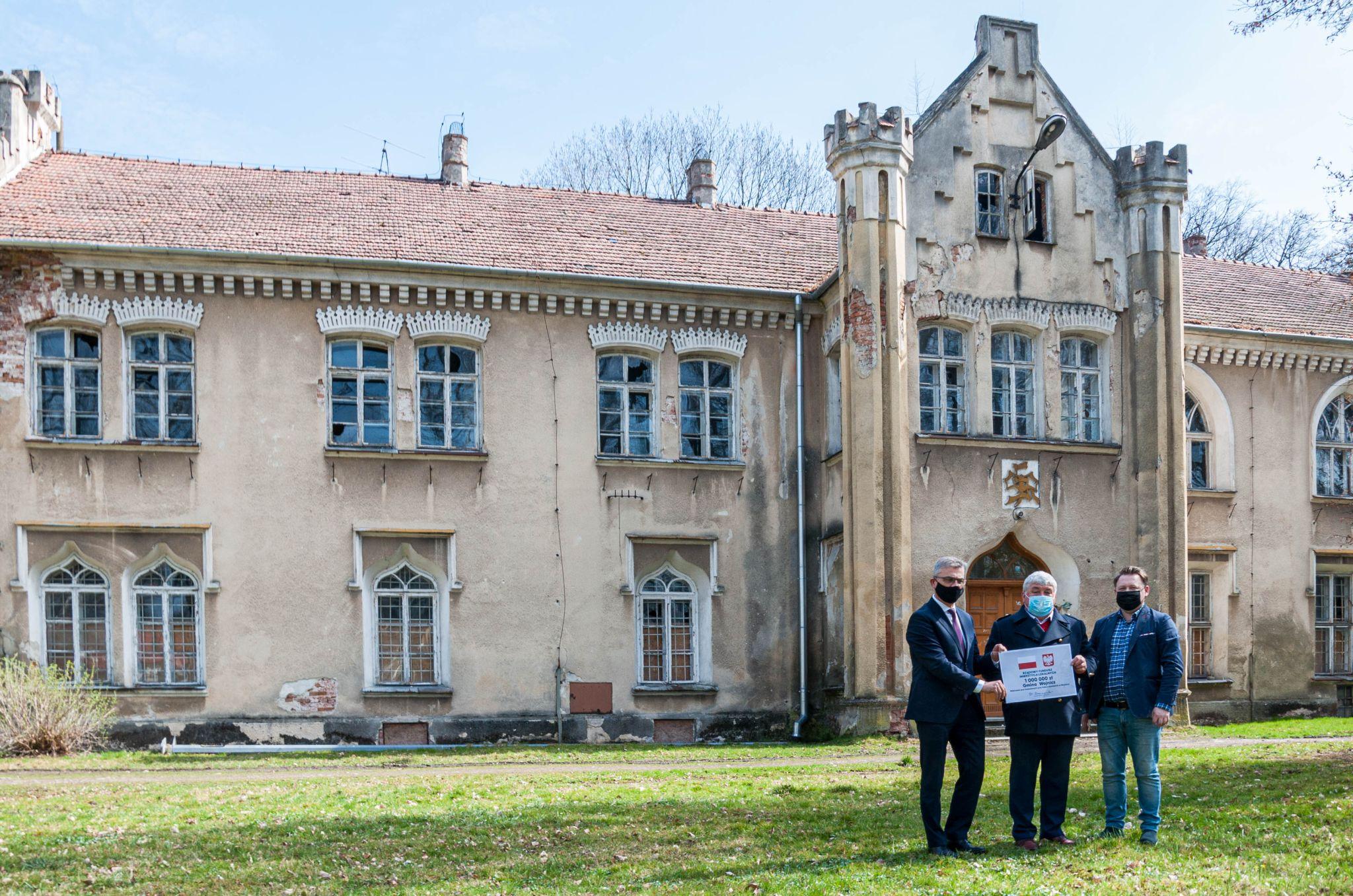 Zdjęcie przekazanie promesy na tle Pałącu Dąbskich w Wojniczu.