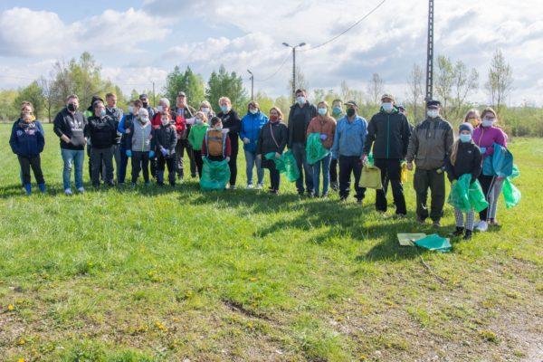 Wiele osób stojących na trawie w rękach trzymających worki na śmieci